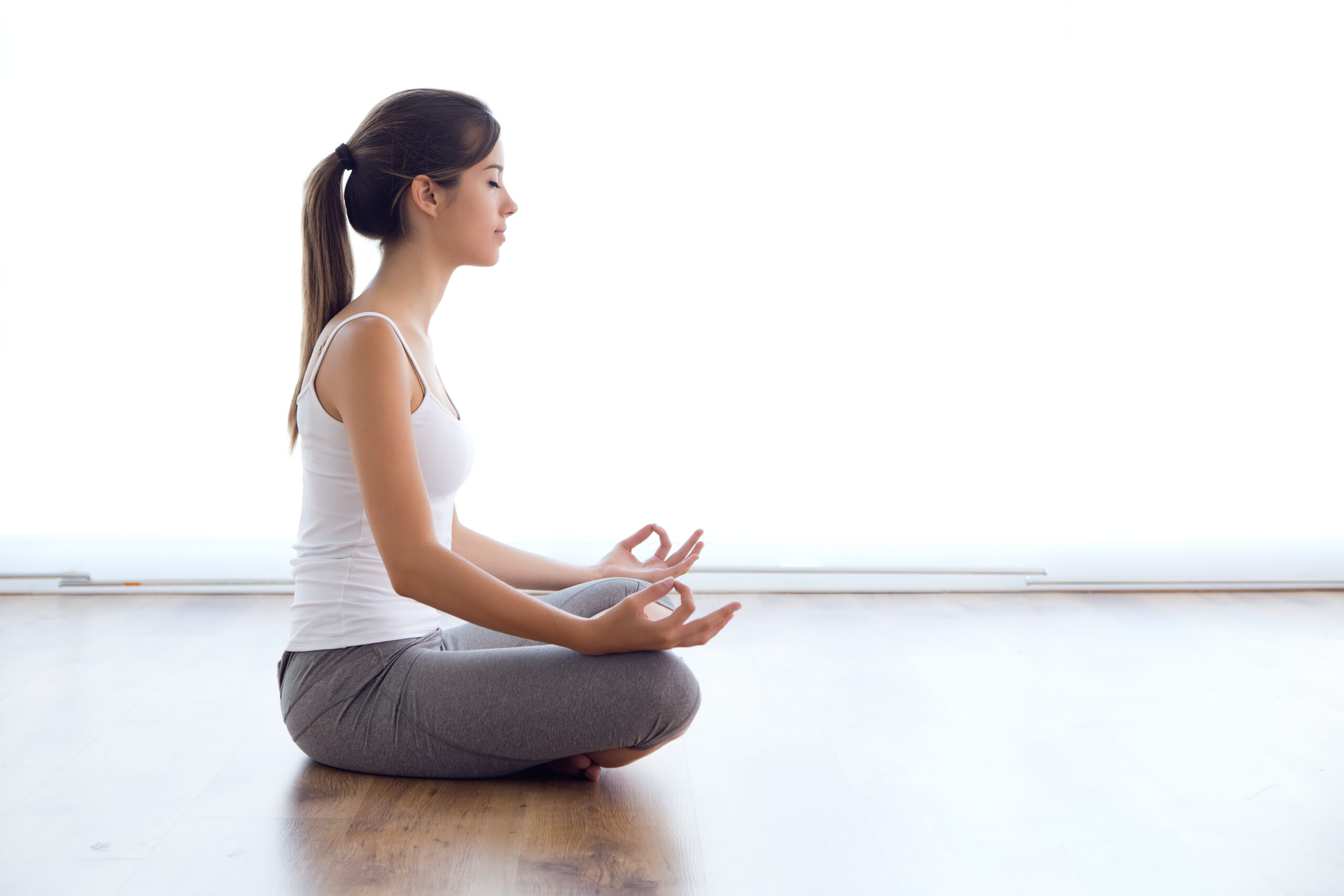 Portrait of beautiful young woman doing yoga exercises at home.