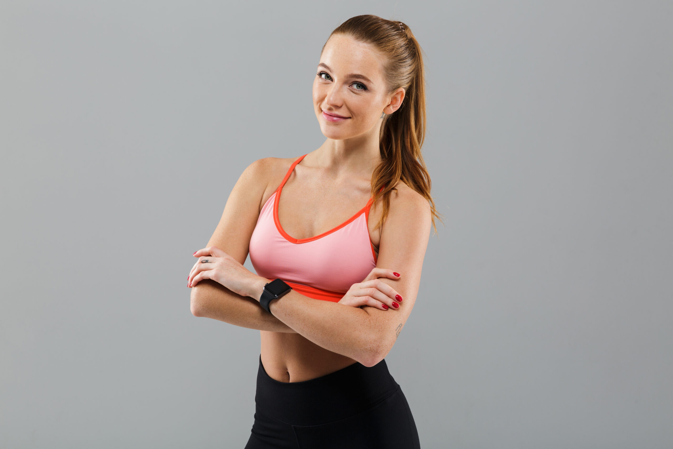 Photo of cheerful young sports woman standing isolated over grey background. Looking camera with arms crossed.