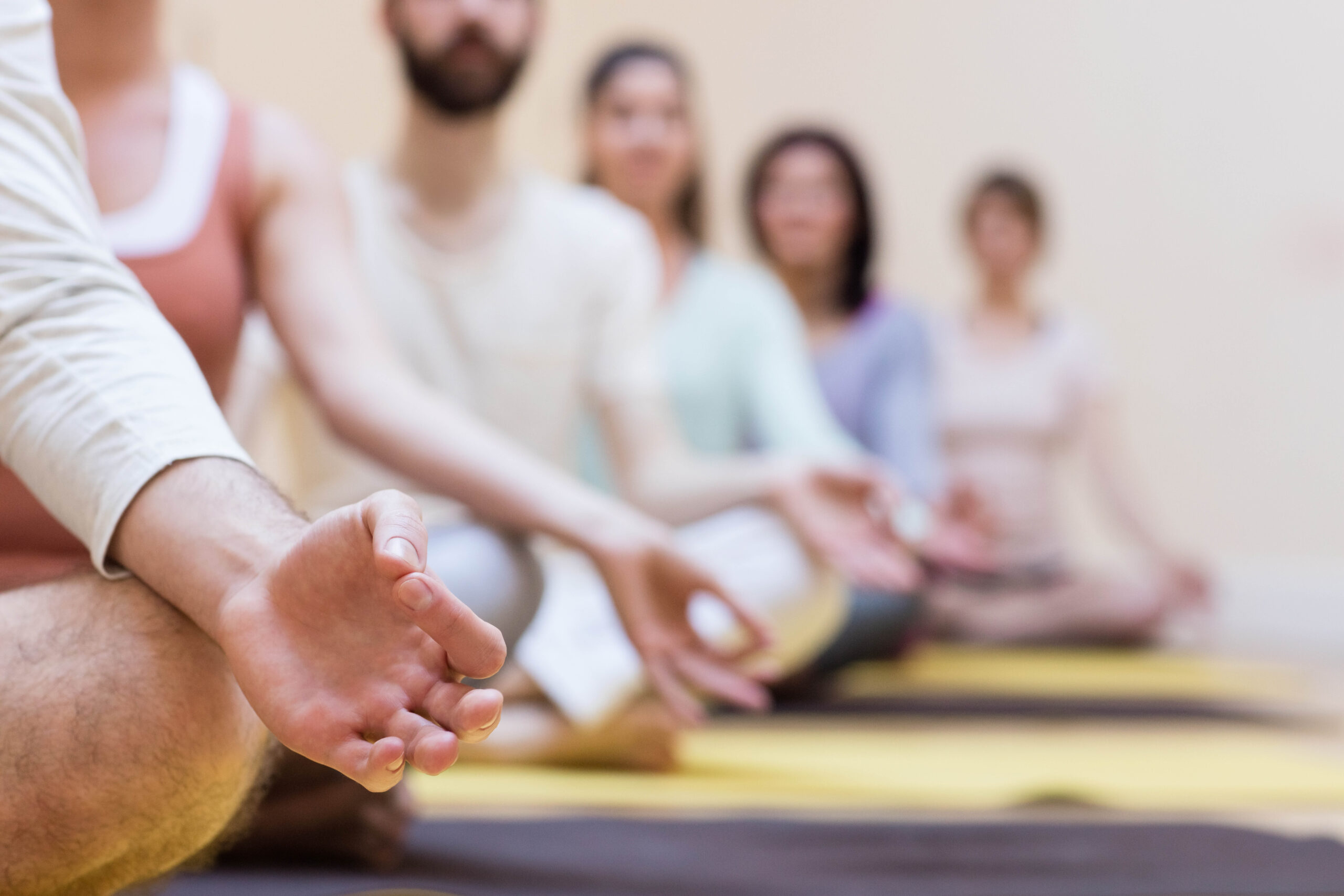 Group of people doing meditation on exercise mat in the fitness studio