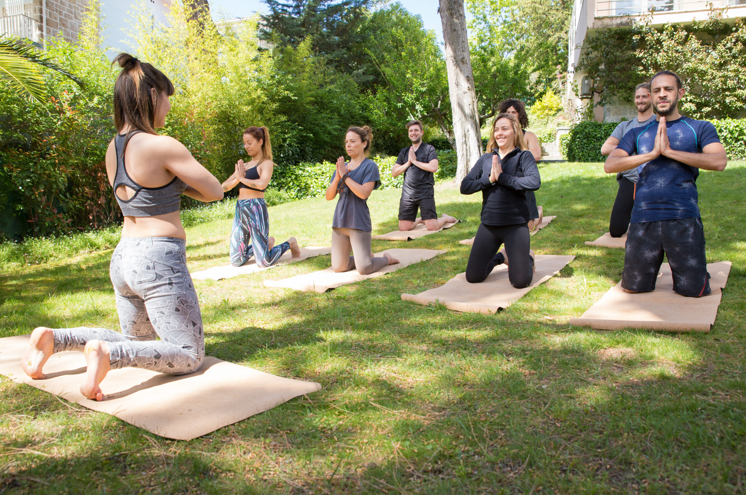 Peaceful people enjoying yoga practice on grass. Men and women kneeling on mats and put hands together in Namaste gesture. Meditation concept