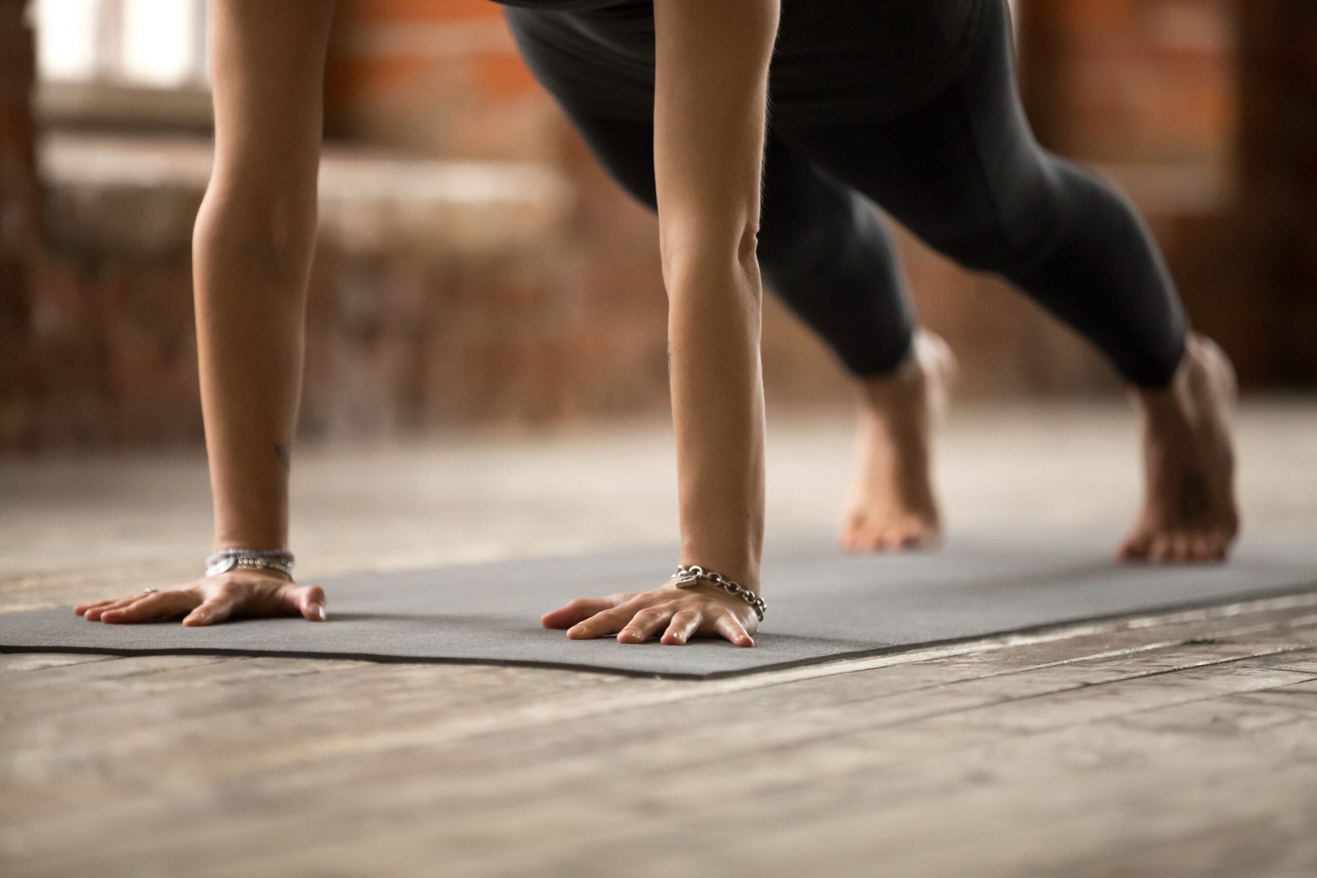 Young sporty woman practicing yoga, doing Push ups or press ups exercise, phalankasana, Plank pose, working out, wearing sportswear, black pants, indoor close up view, yoga studio
