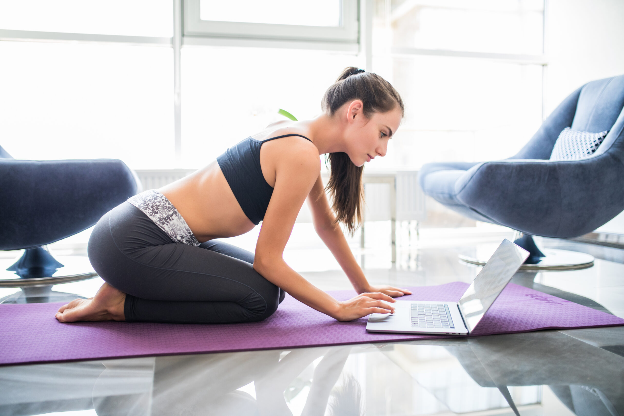 Young woman prepare to make sport look for exercises on laptop at home.